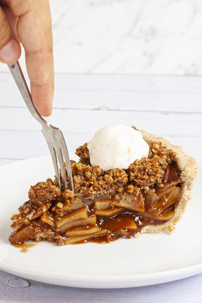 A slice of apple pie on a white plate with brown sauce, apple slices, crumbly topping and a scoop of white vanilla ice cream. There is a fork taking the first bite.