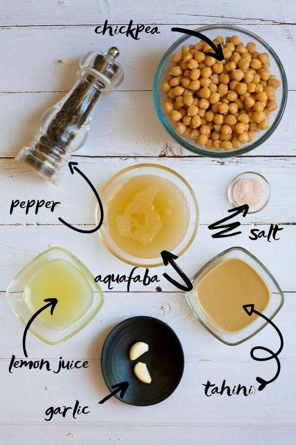 All ingredients of gluten-free hummus measured in bowls.