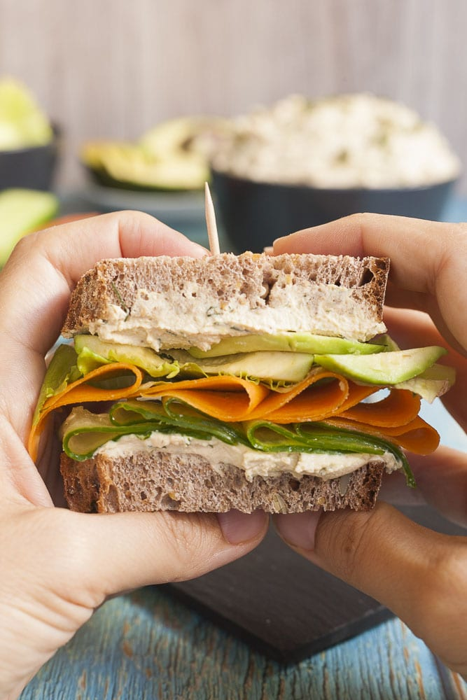 Close-up of a a sandwich with two layers of tofu cream cheese with thinly sliced cucumber, carrot, lettuce and avocado slices