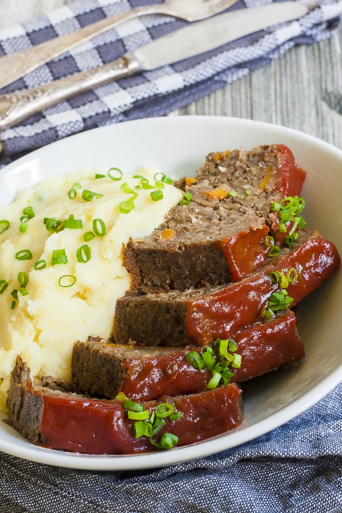 White bowl with mashed potatoes and 4 slices of vegan lentil loaf with maple tomato glaze