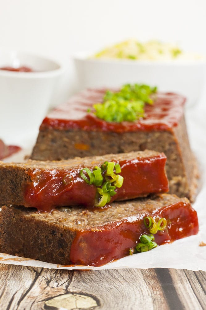 Vegan lentil loaf on parchment paper with maple tomato glaze and chopped spring onion.