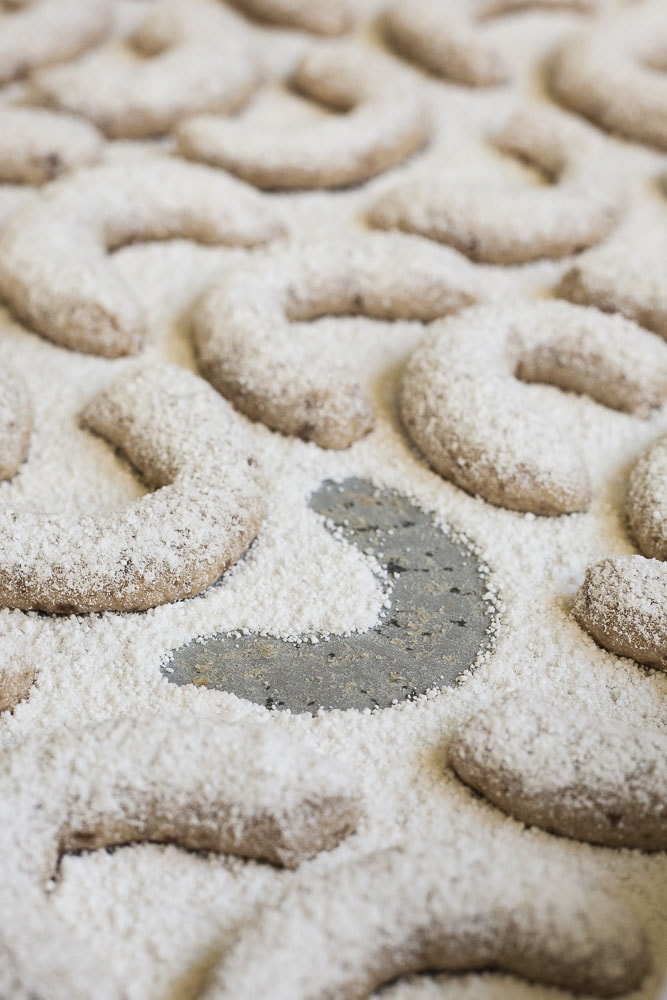 Lots of walnut crescent cookies dusted with vanilla sugar on a parchment paper