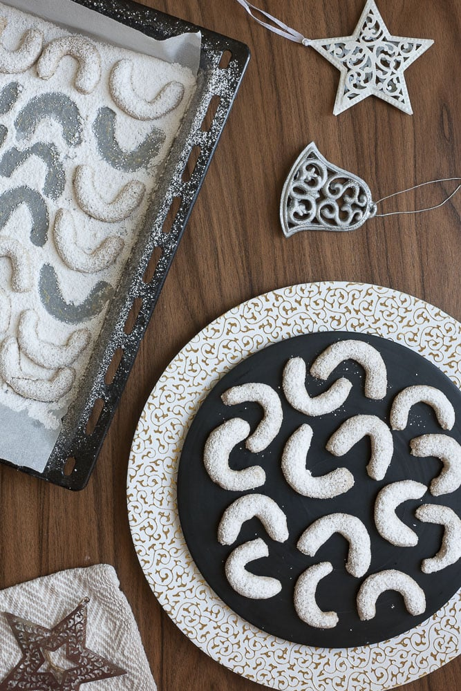 Walnut crescent cookies on a black and white Christmas plate next the the baking sheet pan with the remaining cookies