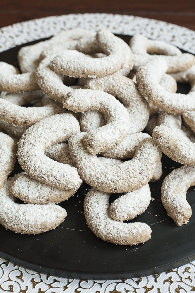 Stack of walnut crescent cookies on a black plate