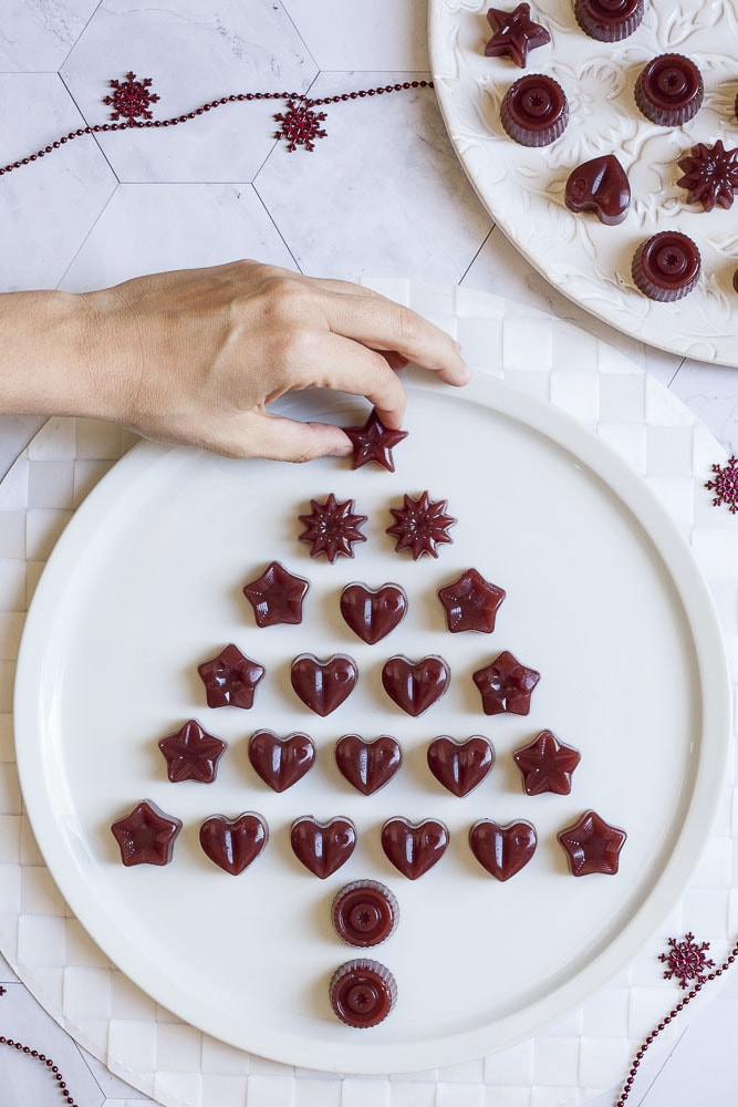 Several type of cranberry jelly shaped as hearts or stars scattered around to form a Christmas tree from above