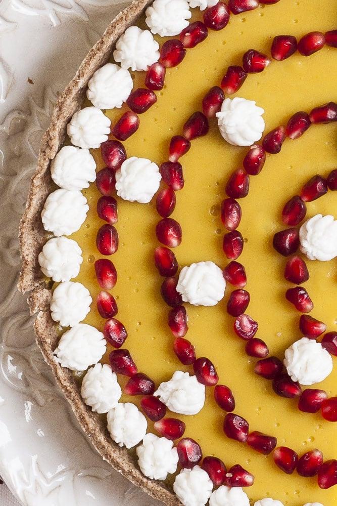 Close-up of an uncut vegan custard tart on a white plate