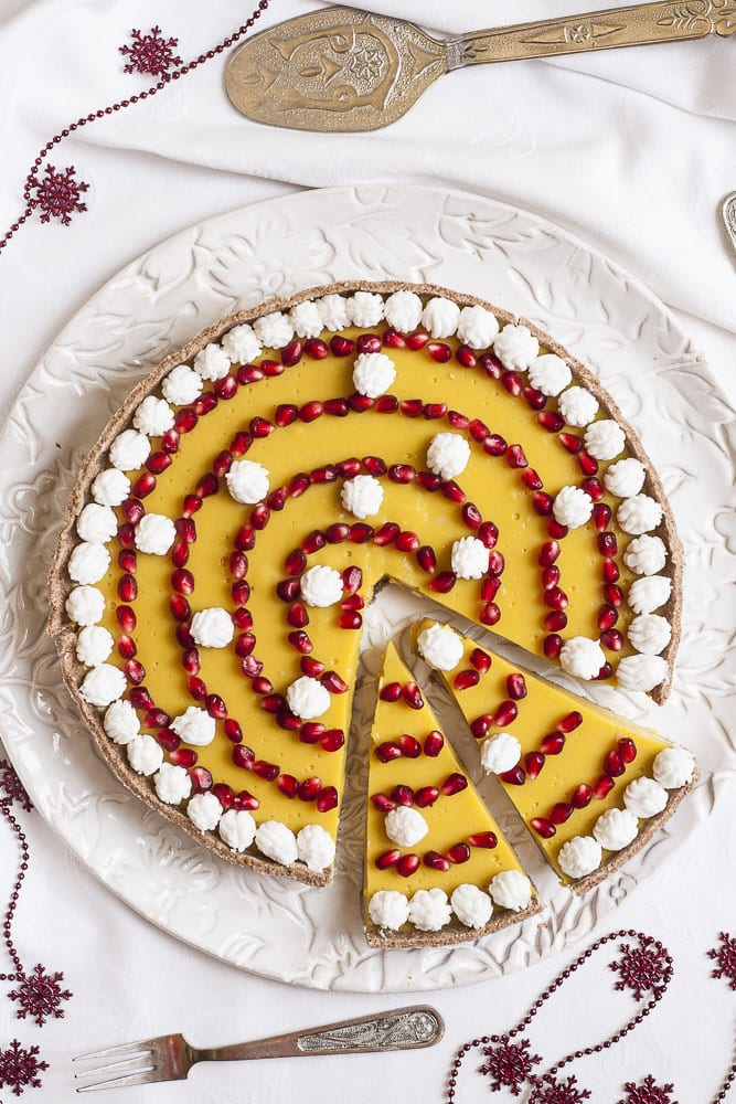 Vegan custard tart topped with pomegranate seeds and cocontu whipped cream on a white serving plate. Two slices have been cut.