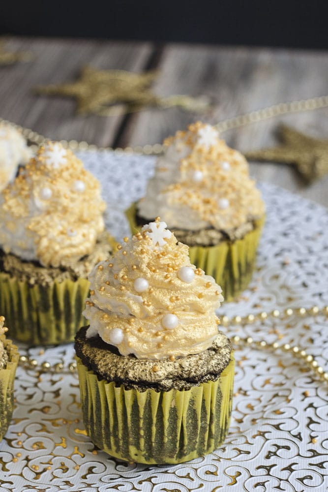 3 vegan gluten-free brownie cupcakes topped with whipped cream and sprayed with gold mist on a festive white and gold plate