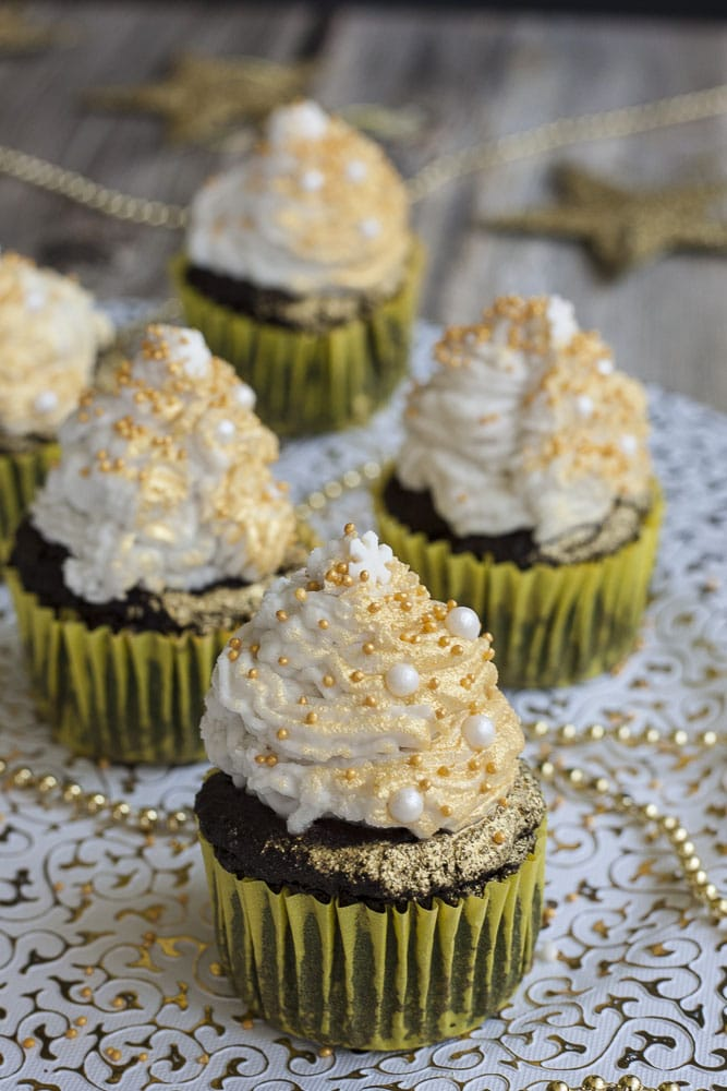 5 vegan gluten-free brownie cupcakes topped with whipped cream and sprayed with gold mist on a festive white and gold plate