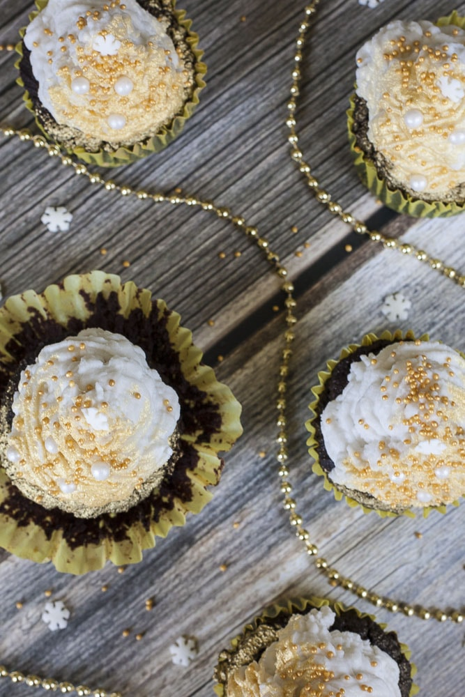 4 vegan gluten-free brownie cupcakes topped with whipped cream and sprayed with gold mist pictured from above