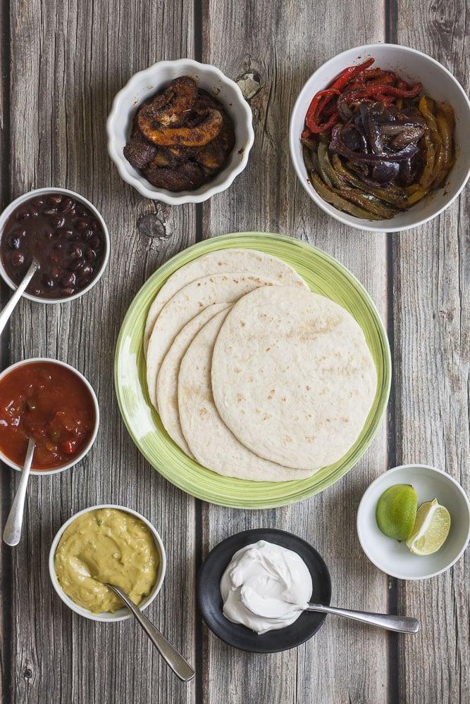 Several bowls showing the ingredients of fajitas: tortilla, fajitas veggies, mushroom slices, bean, salsa, guacamole, sour cream and lime