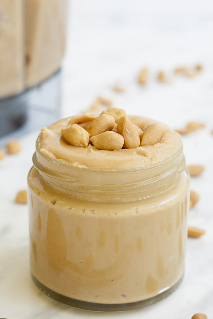 Close-up of a jar of peanut butter topped with peanuts