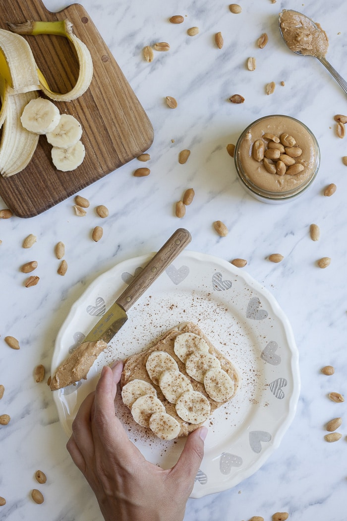 Slice of toast topped with peanut butter, banana slices and cinnamon on a white plate with grey hearts. The jar, the knife and the banana are placed around
