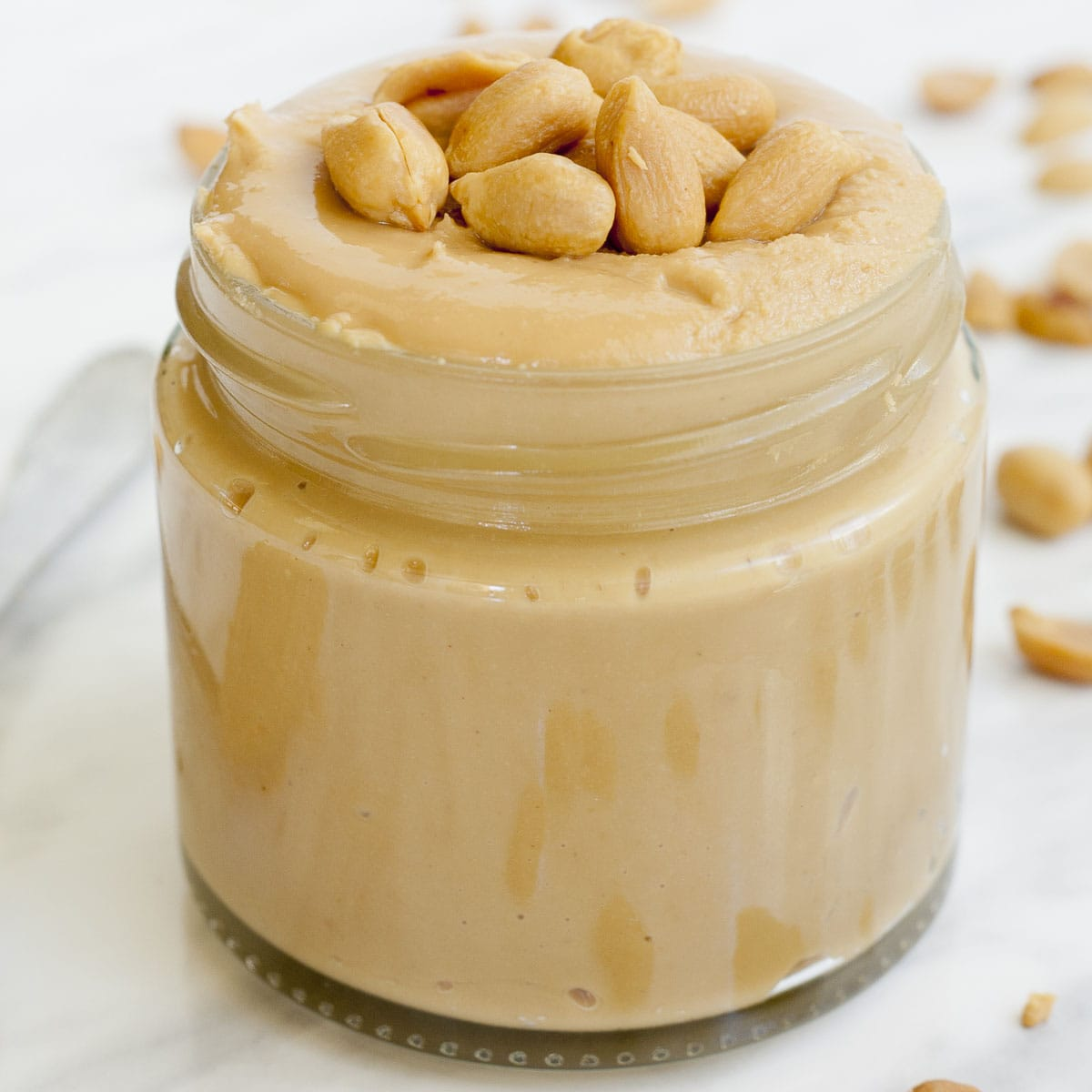 Close-up of a jar full of homemade peanut butter topped with peanuts