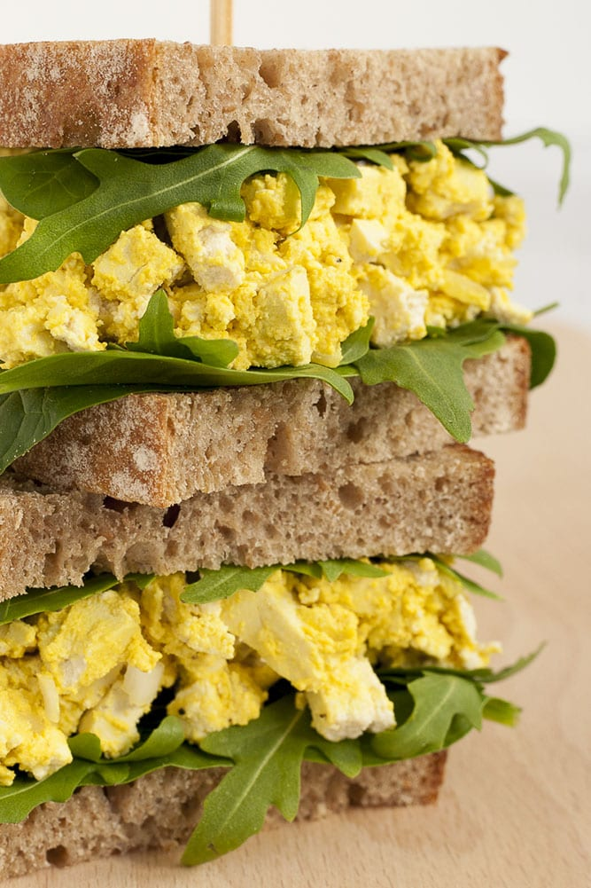 Close-up of two vegan egg salad sandwiches on top of each other with spinach and arugula leaves