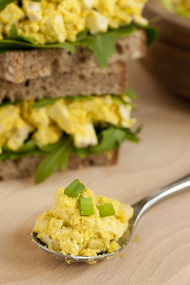 A spoon full of vegan egg salad up close. Two tofu egg salad sandwiches behind.