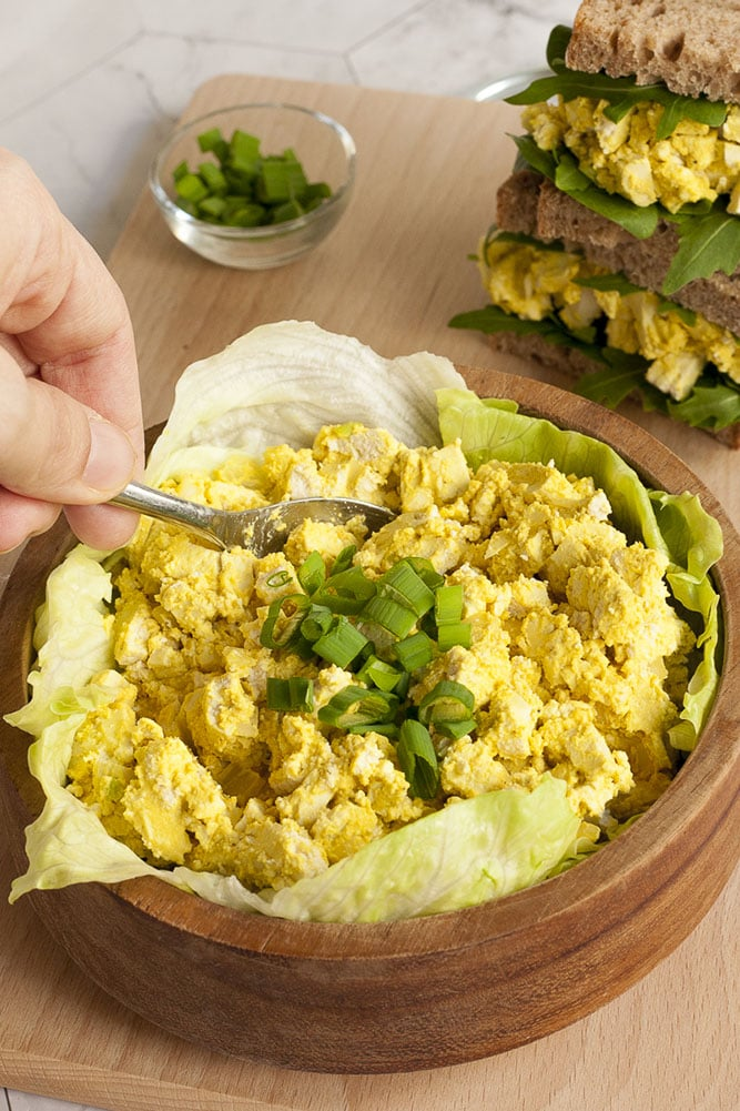 Tofu egg salad in a wooden bowl topped with chopped spring onion