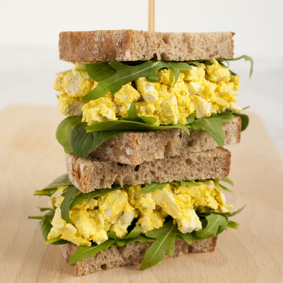 Two vegan egg salad sandwiches on top of each other with arugula and spinach leaves
