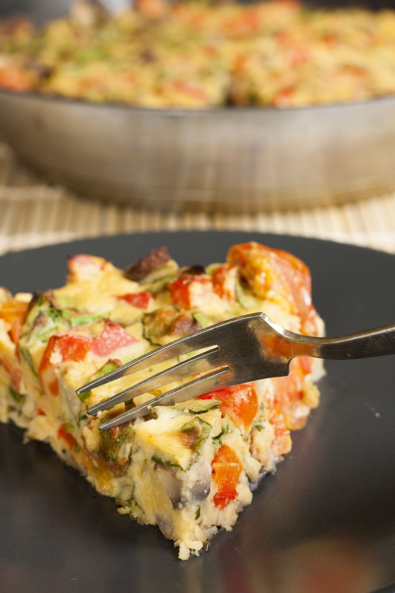 A slice of vegan frittata on a black plate and a fork taking a bite