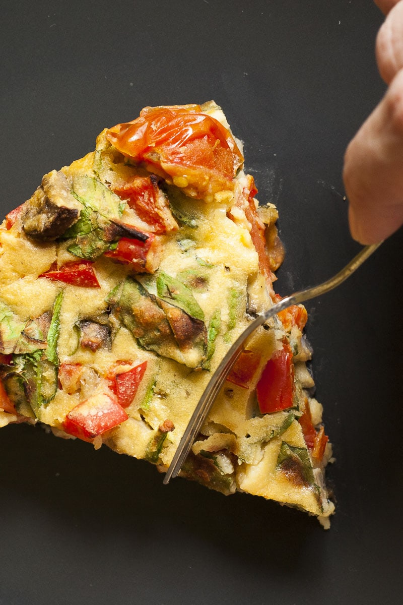 Slice of vegan frittata with a hand taking a spoonful