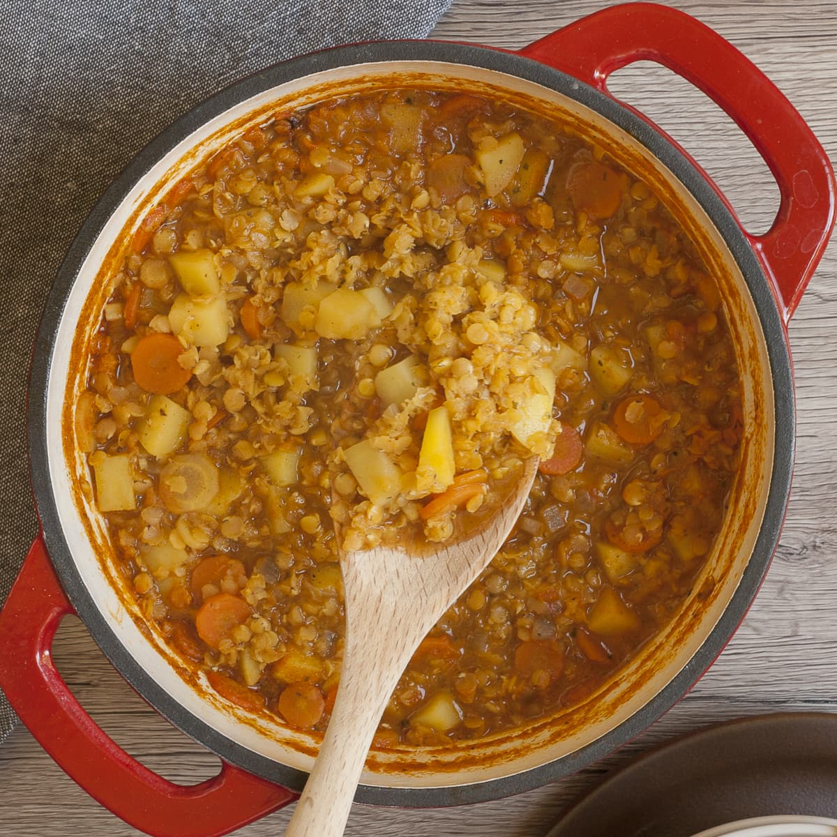 Red Dutch Oven with red lentil soup and a wooden spoon taking a serving