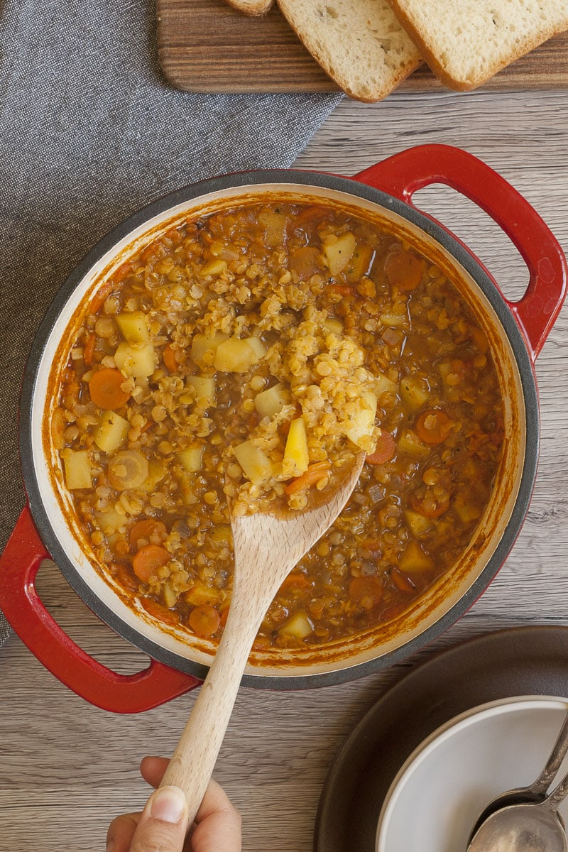 Red Dutch Oven from above with red lentil soup and a wooden spoon