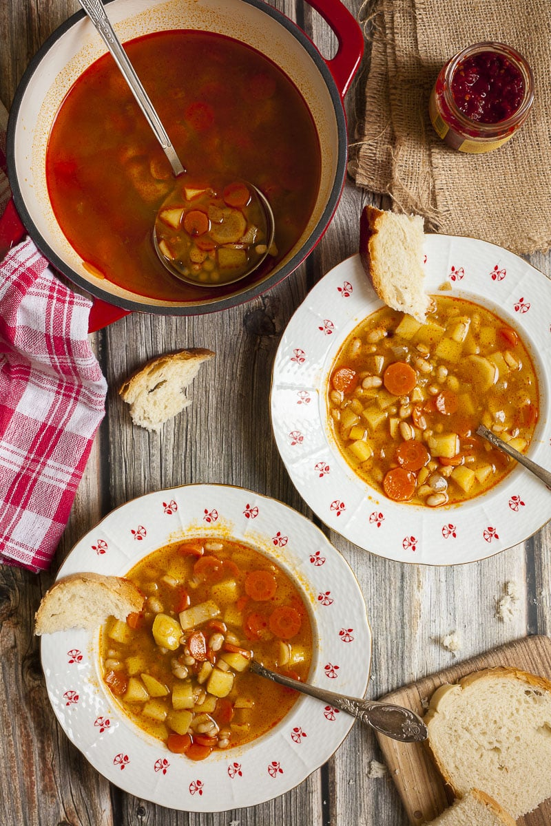 Two plates of hungarian bean goulash with spoons and bread slices around