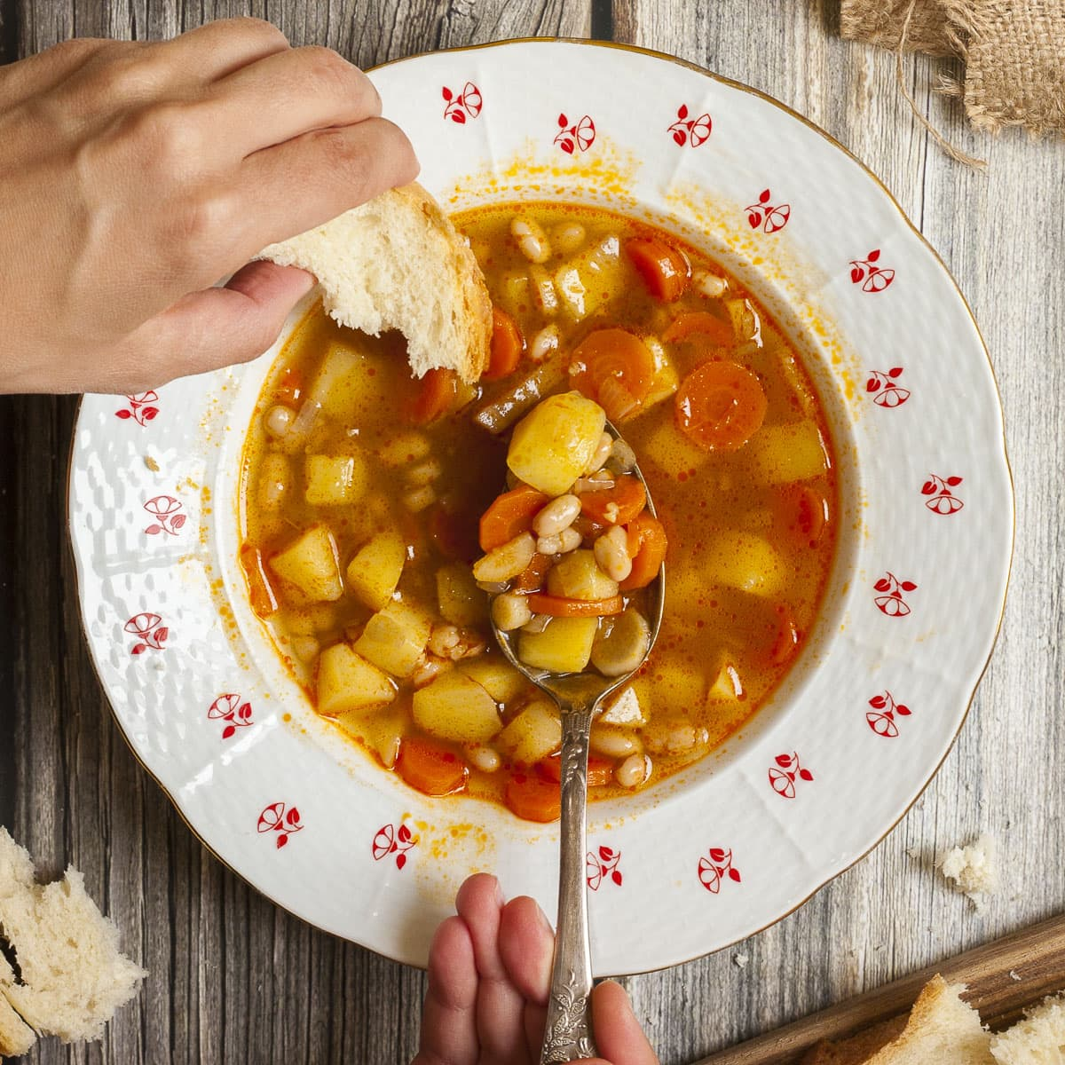 Vegetarian Hungarian Goulash Soup in a white bowl with Hungarian patterns. A hand is taking a spoonful and dunks a bread slice