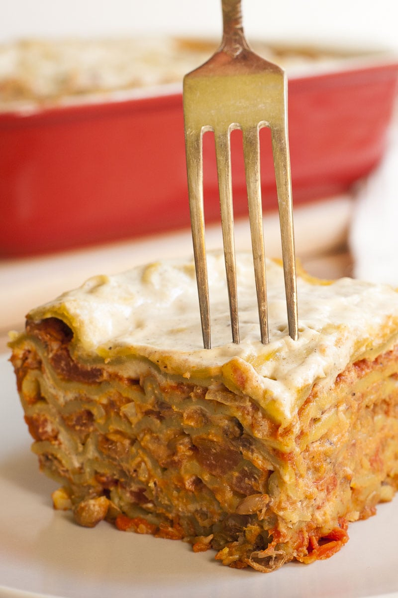 A slice of vegan lasagna and a fork which takes the first bite.