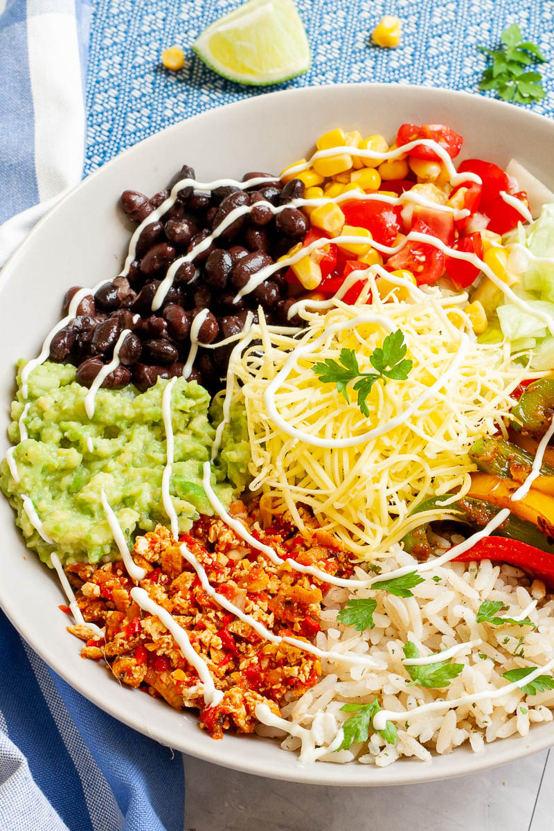 A large white plate in the middle with colorful ingredients like black beans, corn, shredded cheese, bell pepper strips, rice, shredded lettuce, avocado.