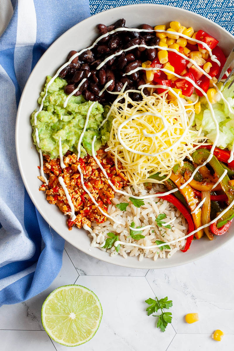 A large white plate in the middle with colorful ingredients like black beans, corn, shredded cheese, bell pepper strips, rice, shredded lettuce, avocado. Blue white table clothes with scattered corn and lime wedges.