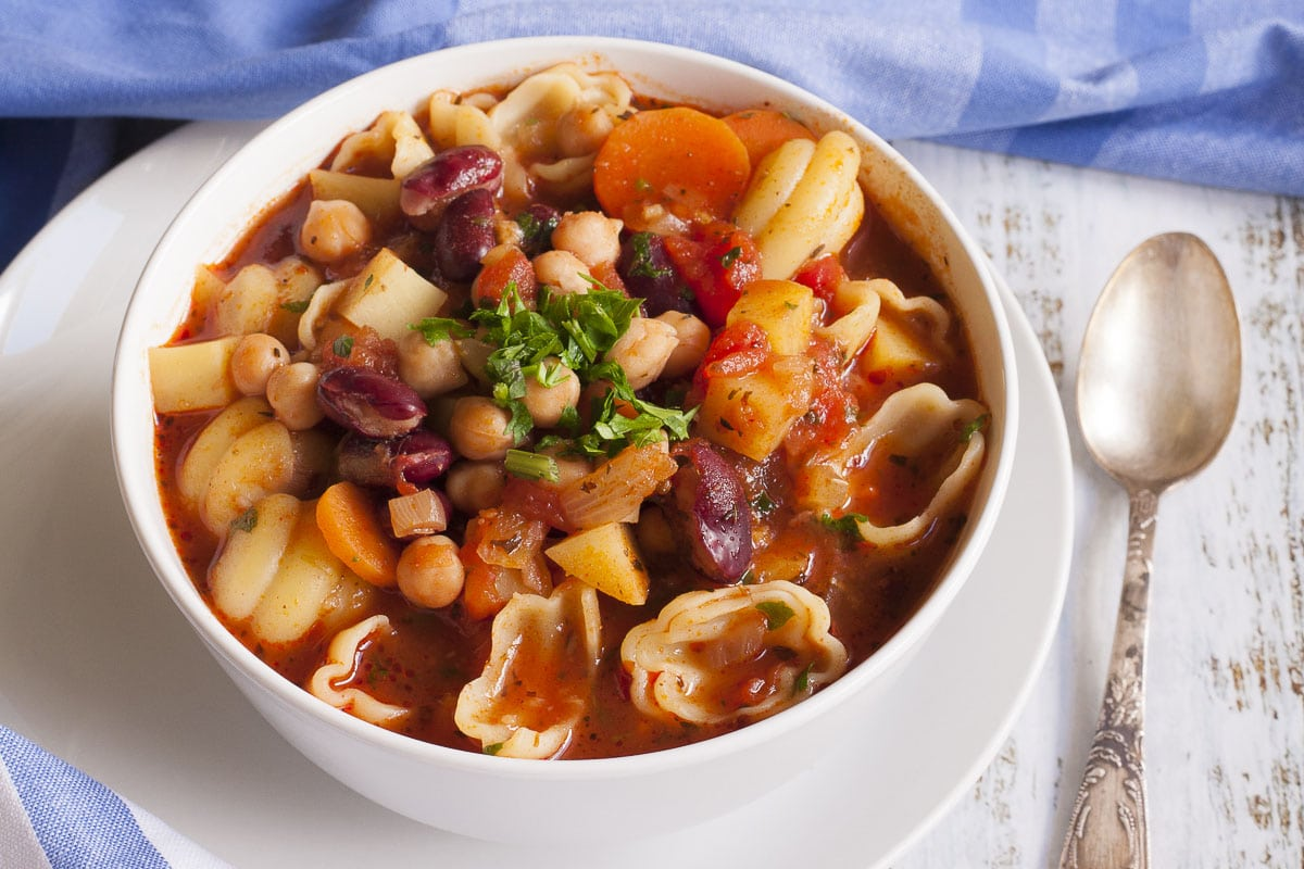 Vegan minestrone soup in a white bowl with a spoon next to them.