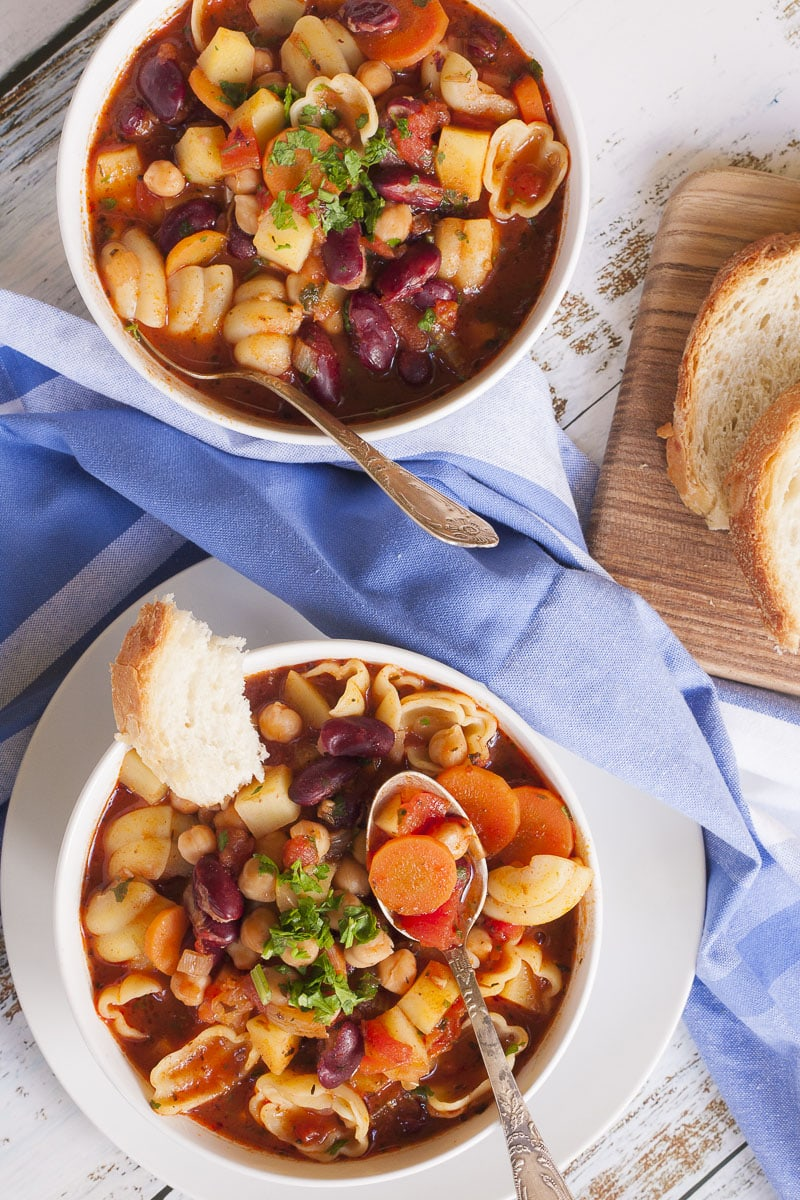 Two white bowls of veggie-packed Italian minestrone soup with a blue tablecloth in between.