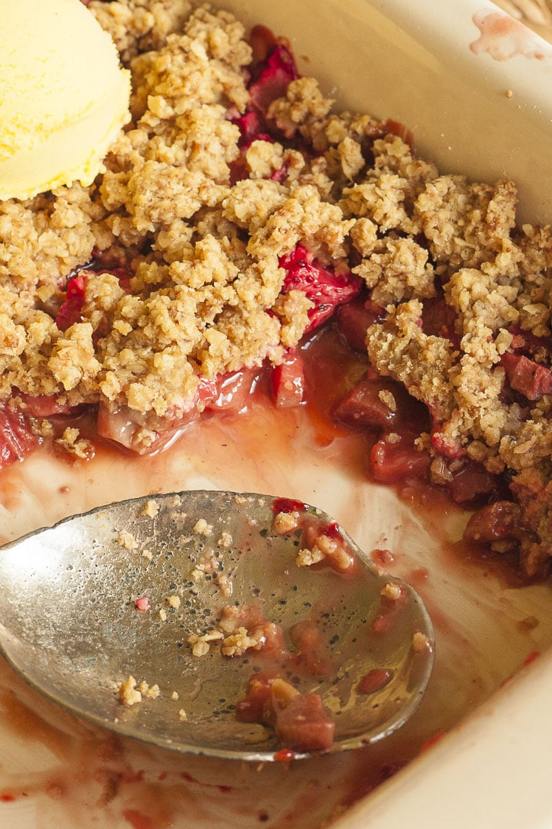 A white baking dish with red fruity sauce and brown crisp up close with a serving spoon in the middle