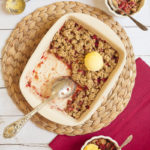 A white rectangle baking dish from above with brown crumb-like topping and red sauces peaking out of it. It is topped with one scoop of vanilla ice cream. 2 small white bowl is next to it with red fruity sauce and brown crisp and vanilla ice cream