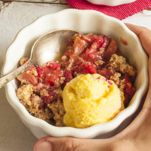 A hand is holding a small white bowl with red fruit, brown crisp topping and vanilla ice cream.