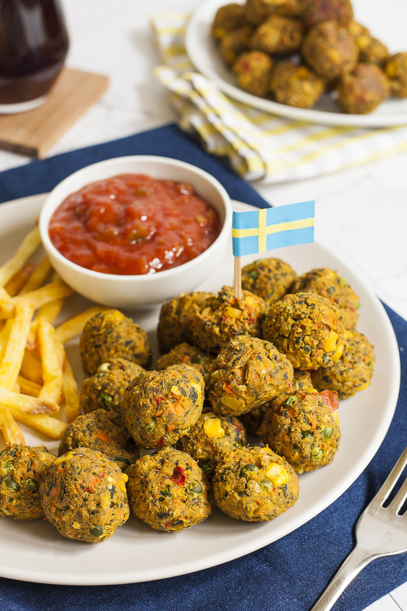 White plate full of small colourful balls with fried potato sticks and a small white bowl with red sauce. A blue yellow flag is stuck in one ball