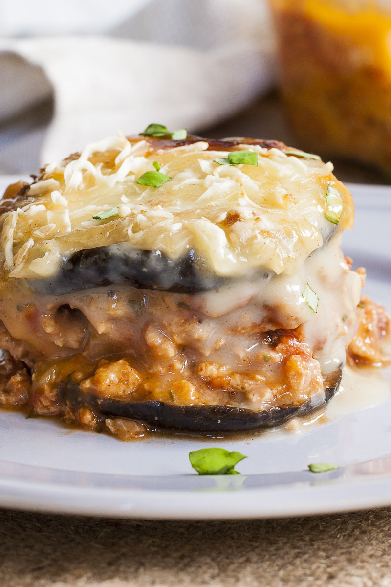 One serving of vegan moussaka is on a light purple plate. You can see the layers of purple eggplant, brown mince and white sauce on top.