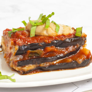 3 slices of purple eggplant in between red and white sauces on a white plate topped with fresh green herbs. In the background there is a red casserole