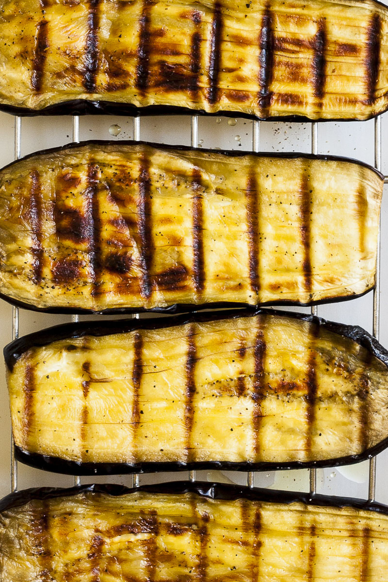 Eggplant slices slightly browned with dark brown lines due to the grill rack it was roasted on.