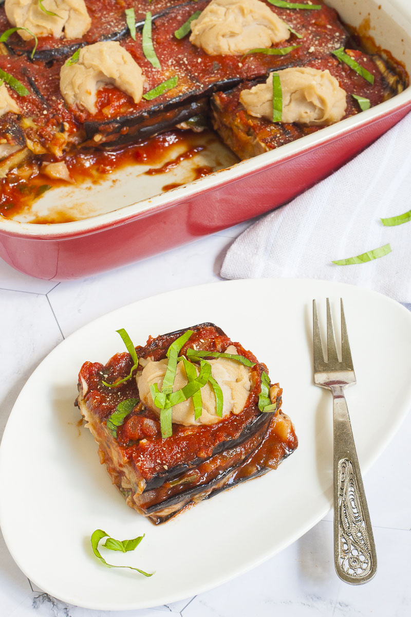 3 slices of purple eggplant in between red and white sauces on a white plate topped with fresh green herbs. In the background there is a red casserole with the remaining eggplant parmesan