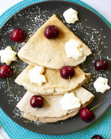 Black plate from top with 3 crepes folded as triangles with cherry and whipped cream scattered on top.