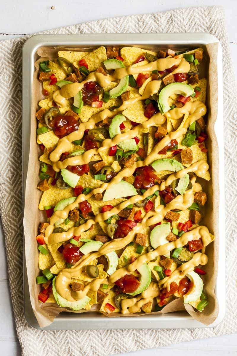Silver sheet pan full of yellow tortilla chips, avocado slices, jalapeno slices, red and yellow sauce.