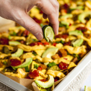 A hand squeezing a lime on top of a silver sheet pan full of yellow, red and green items.