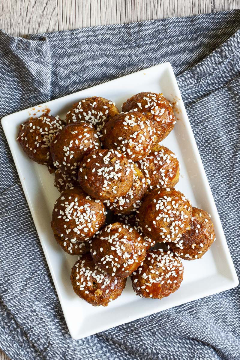 White plate with several brownish-redish balls on top of each other sprinkled with sesame seeds.