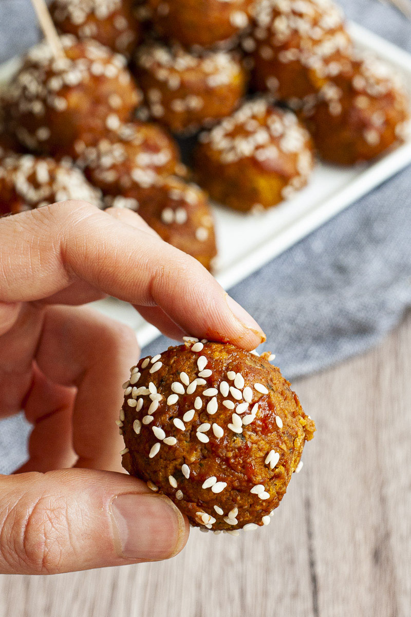 A hand is holding a brown-red ball sprinkled with sesame seeds. In the background more balls on a white plate.