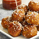 White plate with several brownish-redish balls on top of each other sprinkled with sesame seeds. In the background a small glass jar with red sauce.