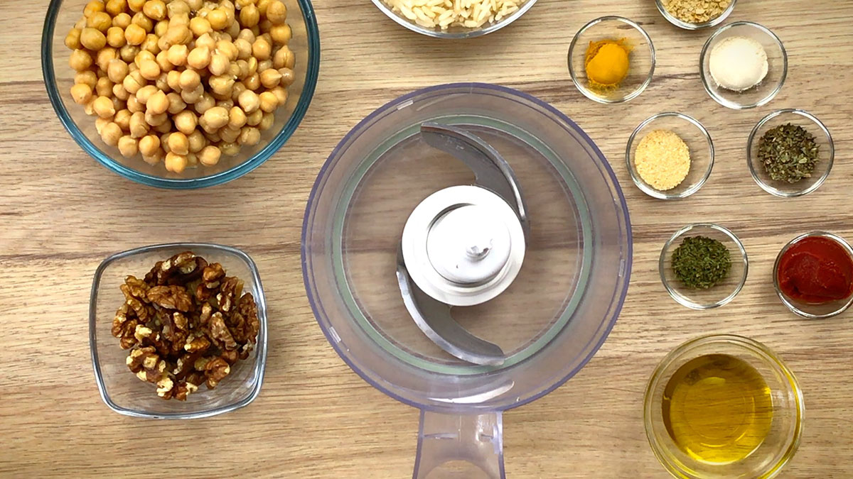 The ingredients of chickpea meatballs are measured in small glass containers 8 for seasoning and 3 for main ingredients. A food processor is empty in the middle.