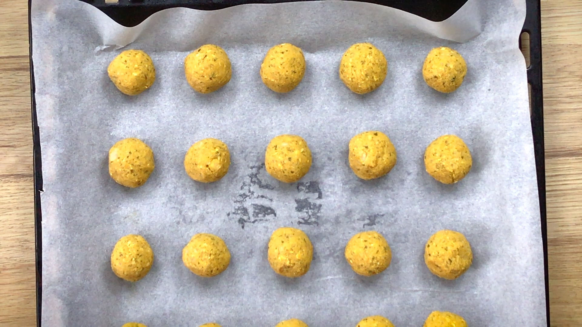 Yellow balls lined on a parchment paper in a sheet pan.