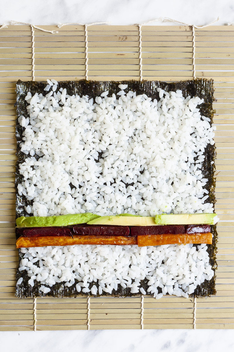 Bamboo mat with green paper-like sheet topped with white rice and colourful sticks of veggies green purple and yellow forming 3 lines.